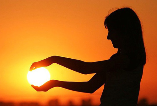 Woman holding the Sun in her hands
